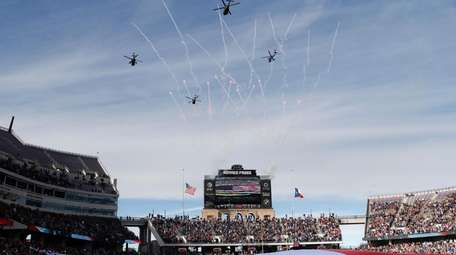 United States military helicopters fly over the stadium