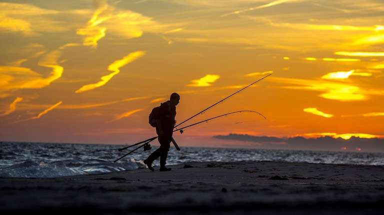 A man leaves the beach after surf fishing