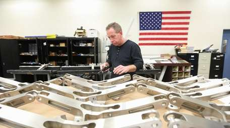 Quality inspector Bob Buhler looks over engine mounts