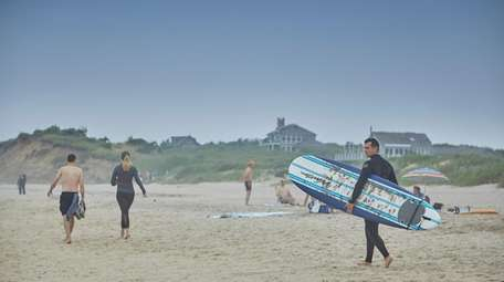 Beachgoers enjoy the surf in Montauk on June