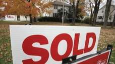 A sold sign stands outside a house in