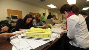 Workers examine individual affidavit ballots at the Nassau