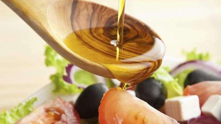 Olive oil is poured over salad.