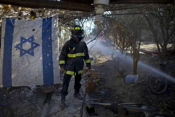 An Israeli firefighter walks past the remains of a house in Yemin Orde.  (AP, via Newsday)