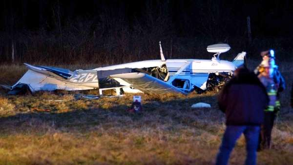 Officials investigate the scene where a plane crashed