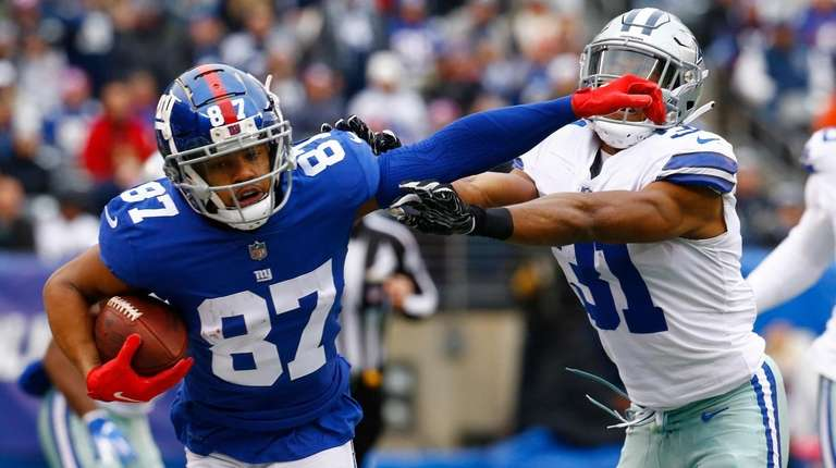 Sterling Shepard of the Giants stiff-arms Byron Jones