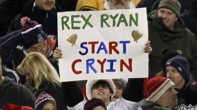 A Patriots fan holds up a sign during