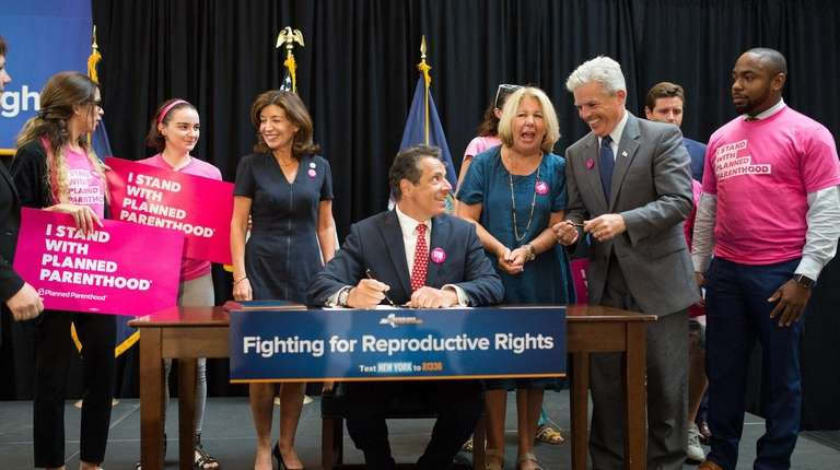 Gov. Andrew M. Cuomo, center, signs a bill