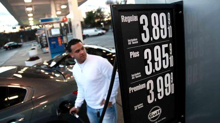 Tristan Robles, of Selden, pumps gas at a