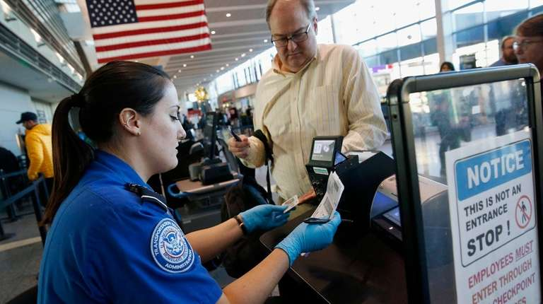 Transportation Security Administration officer Darby Finch checks boarding