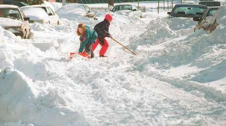 Annie, 13, and Katie, 10, attempt to shovel