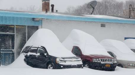 Snowdrifts pile up on top of cars at