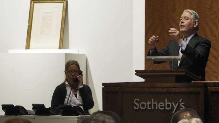 Auctioneer David Redden conducts bidding for a copy