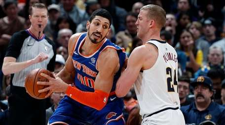 Knicks center Enes Kanter, left, is defended by