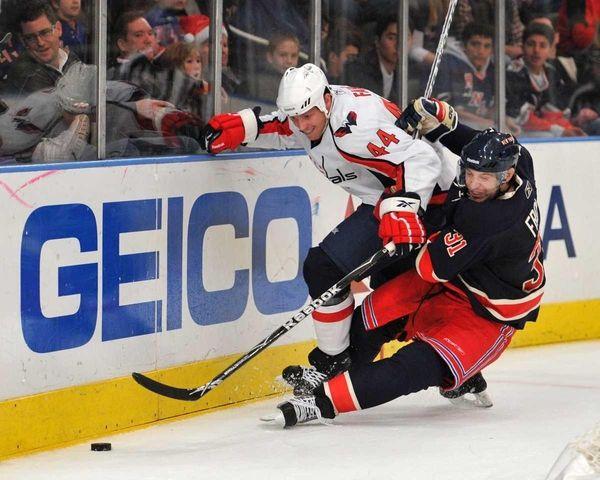 Rangers' Alex Frolov wrestles along the boards against
