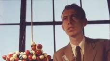 James Watson with a molecular model of DNA