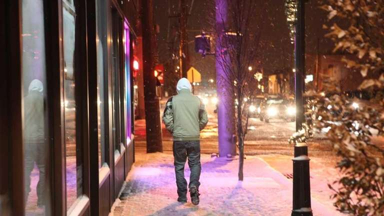Pedestrians navigate a snowy Jericho Turnpike Tuesday morning