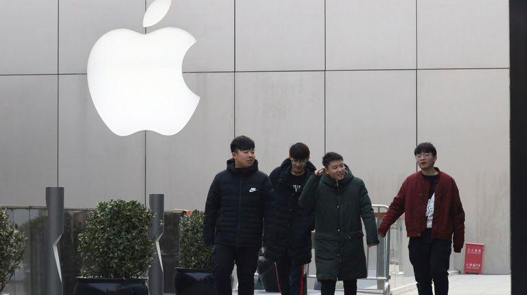 Pedestrians walk past the Apple logo in Beijing,