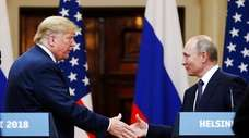 President Donald Trump shakes hand with Russian President