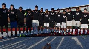 Mineola varsity boys soccer teammates gather around the