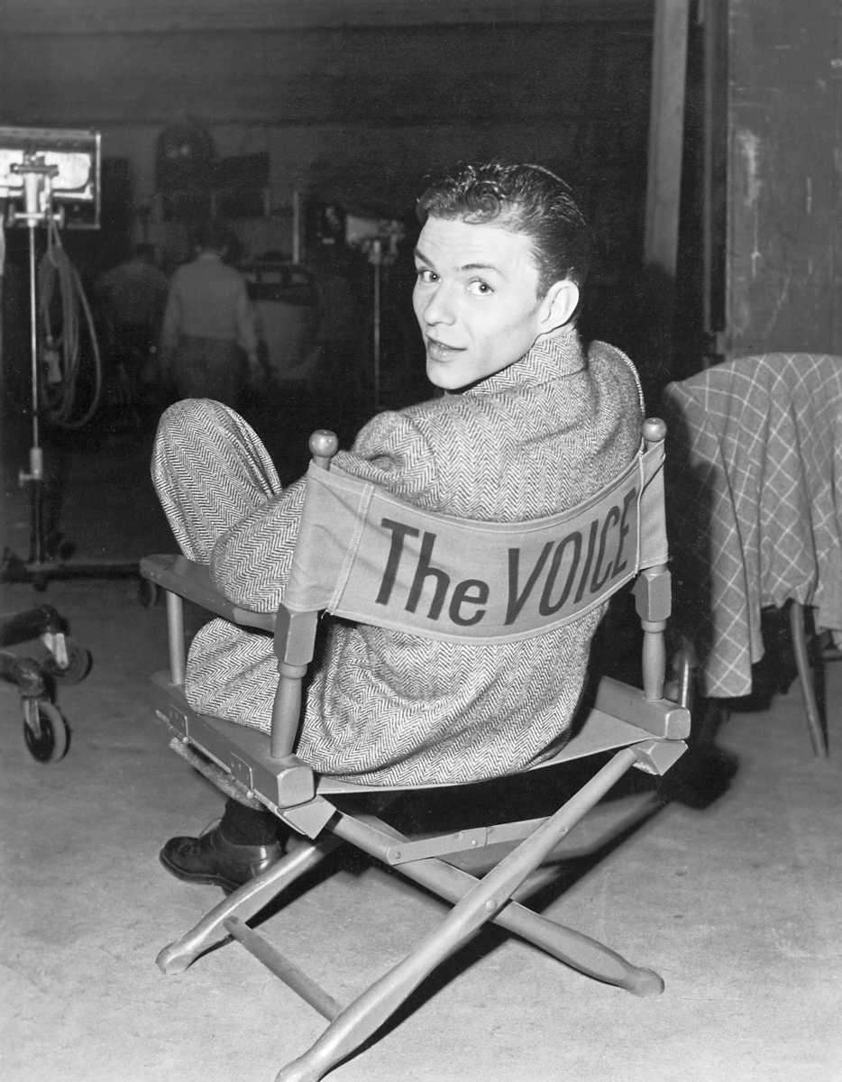 Frank Sinatra is seen sitting in a director's