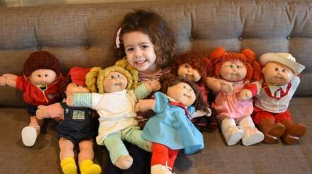 Casey O'Hara, 3, cuddles with Cabbage Patch Kids