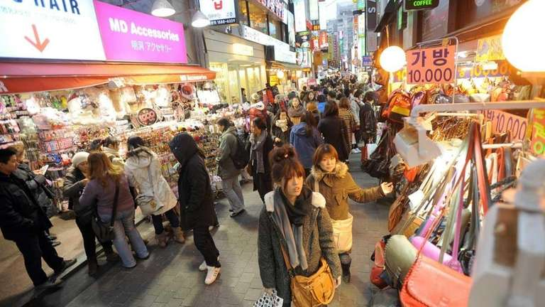 Shoppers browse through goods in a shopping district