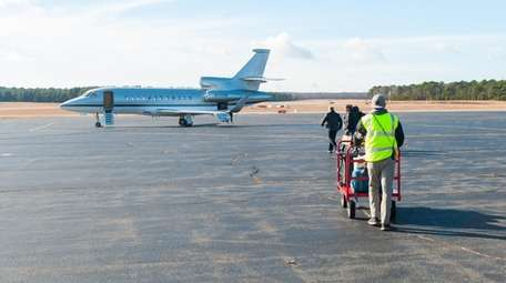 Luggage is taken to a jet at East