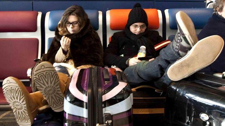 Travelers wait at JFK airport while flights were