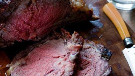 Standing rib roast of beef is sliced on