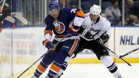 The Islanders' Travis Hamonic plays the puck against