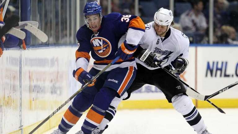 The Islanders' Travis Hamonic plays the puck against