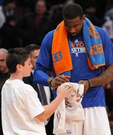 Knicks center Amar'e Stoudemire signs an autograph for