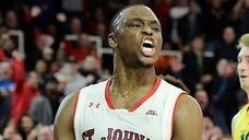St. John's Mustapha Heron celebrates his dunk against