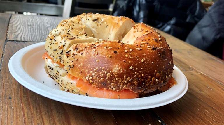 An everything bagel is filled with smoked salmon