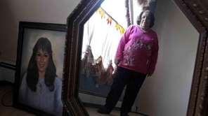 Connie Napoli stands next to a photo of