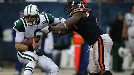 The Jets' Mark Sanchez tries to escape from
