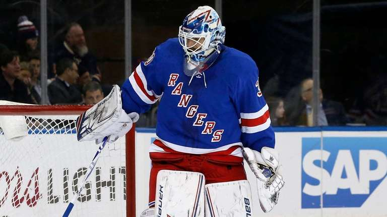 Henrik Lundqvist of theRangers digs the puck out