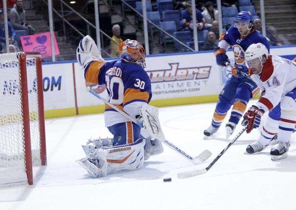 Islanders goalie Dwayne Roloson, left, blocks a shot