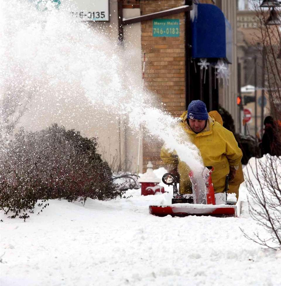 Diego Casimiro uses a snowblower to clear a