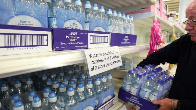 A worker re-stocks shelves with bottles of water