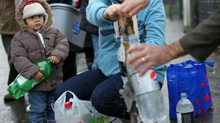 A young child watches holds an empty bottle