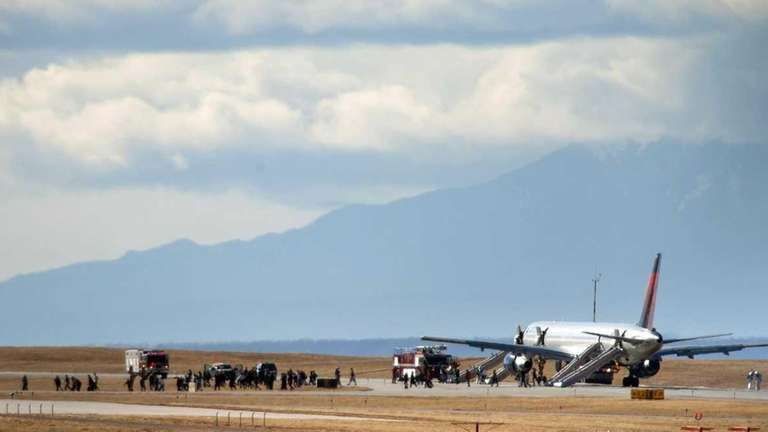 Passengers are led away from a plane that