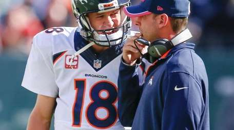 Broncos quarterback Peyton Manning talks with offensive coordinator