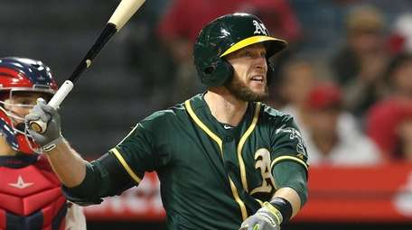 A's second baseman Jed Lowrie watches his hit