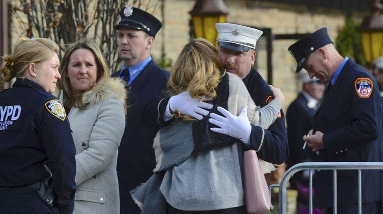 Mourners embrace at the wake held for firefighter