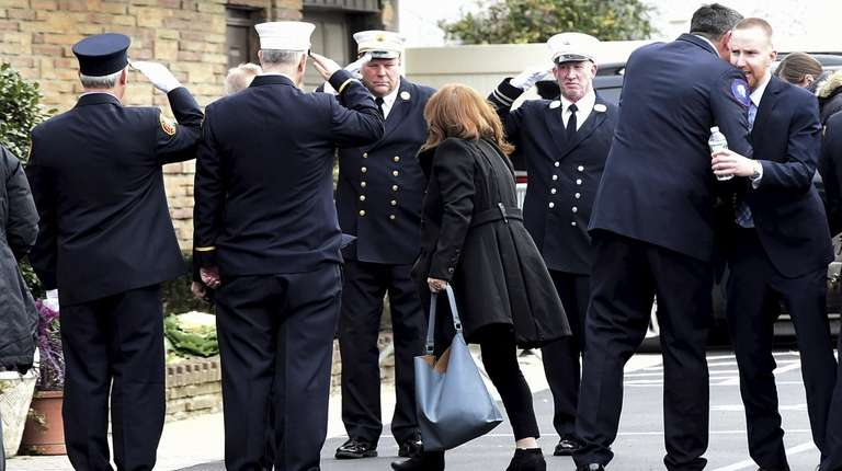 Firefighters salute family members arriving for wake of