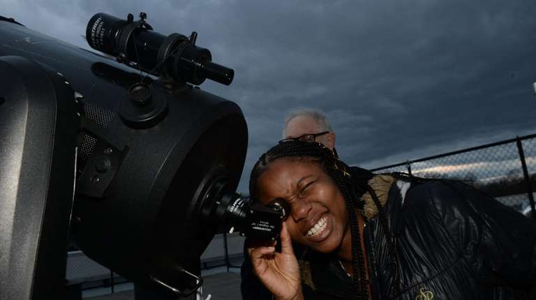Foyinsi Adegbonmire, 22, looks through a telescope at