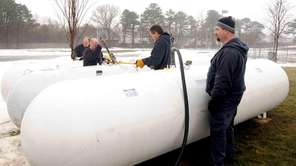 Synergy Gas Company workers install temporary tanks behind