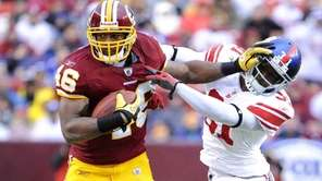 Redskins Ryan Torain stiff-arms Giants' Aaron Ross, Sunday.